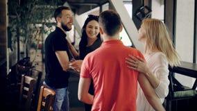 Beeld van jonge mensen in toevallige kledingszitting in de koffie bij barteller Knappe kameraden die bij de lijst zitten die opst stock videobeelden