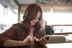 Beeld van jonge vrouwelijke lezing sms op de telefoon in koffie royalty-vrije stock foto's