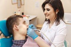 Beeld van jonge vrouwelijke tandarts in witte laag die met mannelijke pati?nt in de tandruimte werken royalty-vrije stock fotografie