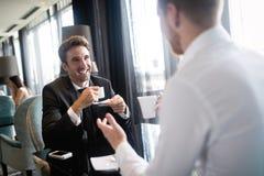 Beeld van jonge zakenman met kop van koffie die met collega communiceren stock foto's