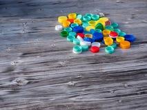 Beeld van kleurrijke plastic kappen op een houten lijst stock afbeelding