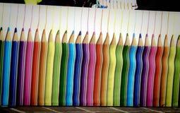 Beeld van kleurrijke potloden op de muur stock afbeelding