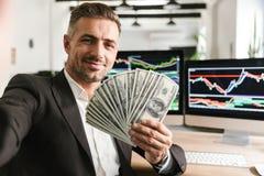 Beeld van knappe het geldventilator van de zakenmanholding terwijl het werken in bureau met grafiek en grafieken aan computer stock foto