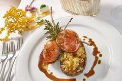 Beeld van lamskoteletten op een bed van groentenaubergine met groenten wordt gevuld die Royalty-vrije Stock Afbeeldingen