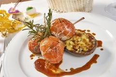 Beeld van lamskoteletten op een bed van groentenaubergine met groenten wordt gevuld die Stock Foto