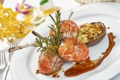 Beeld van lamskoteletten op een bed van groentenaubergine met groenten wordt gevuld die Royalty-vrije Stock Foto