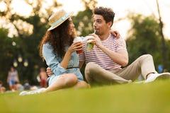 Beeld van man en vrouwenjaren '20 die op groen gras in park en het drinken dranken van plastic koppen zitten stock foto's