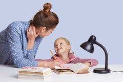 Beeld van moeder en dochterzitting bij lijst door boeken wordt omringd die elkaar met liefde bekijken, die thuiswerk doen samen,  stock foto's