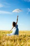 Beeld van mooie blonde jonge vrouw die lange blauwe balkleding dragen en witte kantparaplu houden die omhoog leunend op tarwegebi Stock Fotografie