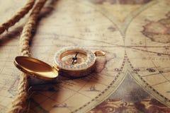 Beeld van oude kompas en kabel op uitstekende kaart Stock Fotografie