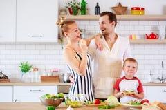 Beeld van ouders en jonge zoon die voedsel in keuken voorbereiden royalty-vrije stock foto