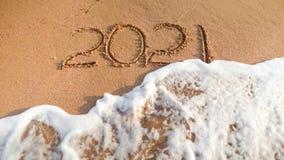 Beeld van overzeese golfwas uit 2021 die aantallen op nat zand bij strand worden geschreven Concept Nieuwjaar, Kerstmis en reis  royalty-vrije stock afbeelding