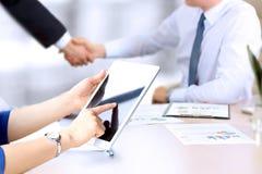 Beeld van partnershandenschudden over bedrijfsvoorwerpen op werkplaats Onderneemster die met digitale tablet werkt stock fotografie