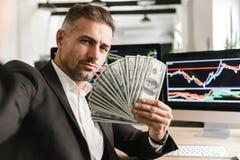 Beeld van rijke het geldventilator van de zakenmanholding terwijl het werken in bureau met grafiek en grafieken aan computer royalty-vrije stock foto's