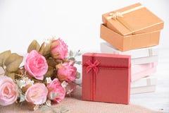 Beeld van rode giftdoos met rood lint met roze roze bloem stock foto's