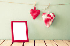 Beeld van rode stoffenharten die op kabel en leeg kader voor houten achtergrond hangen Gefiltreerd Retro Royalty-vrije Stock Foto