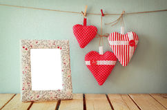 Beeld van rode stoffenharten die op kabel en leeg kader voor houten achtergrond hangen Gefiltreerd Retro Stock Afbeelding