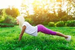 Beeld van sportenvrouw belast met fitness op gazon Royalty-vrije Stock Foto