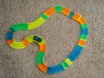 Beeld van stuk speelgoed autospoor met auto en kleurrijke spoorelementen op tapijt stock fotografie