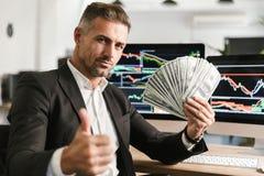 Beeld van succesvolle het geldventilator van de zakenmanholding terwijl het werken in bureau met grafiek en grafieken aan compute stock foto
