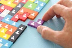 beeld van tangram raadselblokken met mensenpictogrammen over houten lijst, personeel en beheersconcept stock afbeeldingen