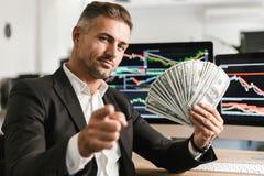 Beeld van tevreden het geldventilator van de zakenmanholding terwijl het werken in bureau met grafiek en grafieken aan computer royalty-vrije stock afbeelding