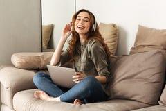 Beeld van tevreden vrouwenjaren '20 met bruin haar die aan muziek luisteren ons Stock Foto