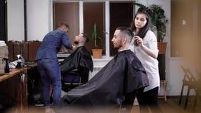 Beeld van twee het jonge knappe mensen zitten behandeld met beschermende kaap op stoelen tegen spiegels bij de herenkapper Mens stock video