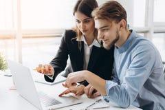 Beeld van twee jonge bedrijfsarbeiders die aan project op kantoor samenwerken stock afbeelding