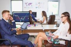Beeld van twee jonge zakenlieden die touchpad op vergadering gebruiken stock foto