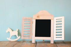 Beeld van uitstekend houten klassiek kader en houten hobbelpaard op houten lijst Gefiltreerd beeld Stock Foto