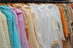 Beeld van vele kleurrijke badjassen op houten hangers in de opslag stock afbeeldingen