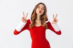 Beeld van verleidelijke meisjesjaren '20 die Kerstmis rode kleding dragen die vredesteken tonen terwijl status, geïsoleerd over w stock afbeelding