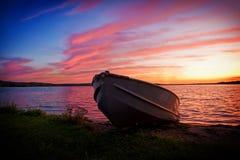 Beeld van vissersboot op kust van meer bij zonsondergang stock afbeeldingen
