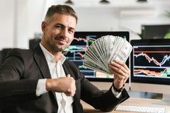 Beeld van volwassen het geldventilator van de zakenmanholding terwijl het werken in bureau met grafiek en grafieken aan computer stock fotografie
