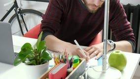 Beeld van vrolijke zakenmanzitting in bureau terwijl het schrijven van nota's het bekijken camera stock footage
