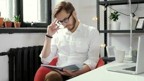 Beeld van vrolijke zakenmanzitting in bureau terwijl het schrijven van nota's het bekijken camera 4K stock video