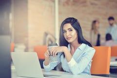 Beeld van vrouw die laptop met behulp van terwijl het zitten bij haar bureau stock foto