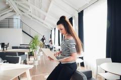 Beeld van vrouw die laptop met behulp van terwijl het zitten in een koffie Volwassen onderneemsterzitting in een zitkamer en het  royalty-vrije stock foto's