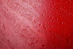 Beelddalingen van een water op een rode metaaloppervlakte royalty-vrije stock afbeeldingen