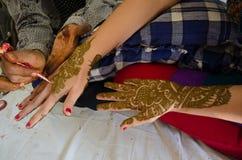 Beelddetail van henna die op hand worden toegepast Stock Foto's