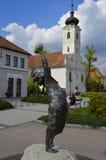 Beeldhouwwerk in Centrum Gödöllö met Kerk Stock Afbeelding