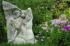 Beeldhouwwerk en bloemen van Flox in de stadstuin royalty-vrije stock afbeeldingen