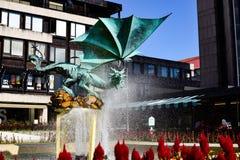 Beeldhouwwerk van een draak op de openbare straat waar een krachtige fontein water op het goddelijke cijfer glanst Royalty-vrije Stock Foto's
