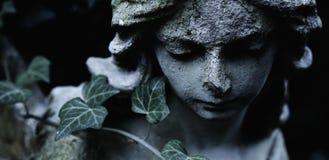 Beeldhouwwerk van een engel met donkere achtergrond Antiek standbeeld Stock Foto