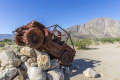 Beeldhouwwerk van een jeep die over een stapel van keien in deser drijven royalty-vrije stock fotografie
