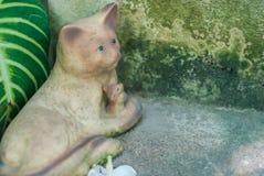 Beeldhouwwerk van een kat die een muis houden zorvuldig dichtbij het oude cement stock foto's