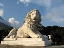 Beeldhouwwerk van een leeuw in de het plaatsen zonstralen Stock Foto's