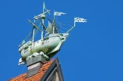 Beeldhouwwerk van een schip over een schoorsteen op een dak Stock Fotografie
