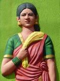 Beeldhouwwerk van Indische landbouwarbeidsvrouw, in traditionele kleding, met de padiebos na het oogsten Stock Foto's